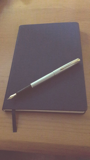 Closed notebook and fountain pen
